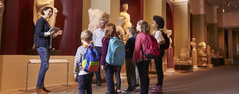 Pupils And Teacher On School Field Trip To Museum With Guide