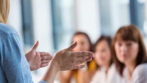 Group of smiling women attending a training. Focus on the female teacher's hand.